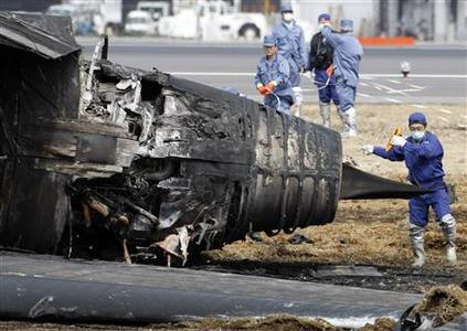 Police officers inspect the site of a cargo plane crash at Narita international airport March 23, 2009. REUTERS/Issei Kato