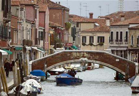 A boat passes a bridge on the island of Murano near Venice January 27, 2009. REUTERS/Chris Helgren