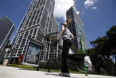 <p>A woman runs in front of the Icon Brickell condo, billionaire Jorge Perez's latest project, in downtown Miami, Florida March 24, 2009. REUTERS/Carlos Barria</p>
