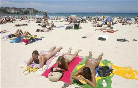 A woman talks with her friends during a sunny morning at Bondi beach in Sydney, December 30, 2008. REUTERS/Daniel Munoz