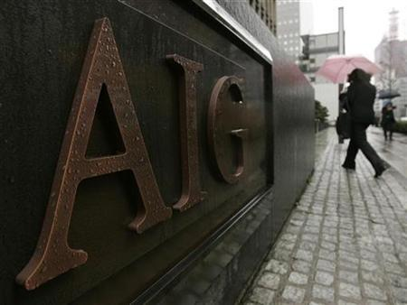 A woman walks past the AIG Building in Tokyo February 27, 2009. REUTERS/Michael Caronna