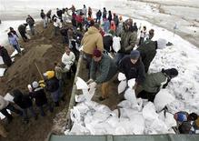 <p>Carl Aakre (C) and Michael Heinecke (blue hat), volunteers from Perham, Minnesota, throw sand bags into the back of a truck for distribution to flood victims' houses at a bagging station in Fargo, North Dakota, March 26, 2009. REUTERS/Eric Miller</p>