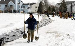 <p>Gerri Dyrdahl walks home after finishing filling sandbags on a levy that protects a neighborhood on the northside of Fargo, North Dakota on the Red River, March 27, 2009. REUTERS/Allen Fredrickson</p>