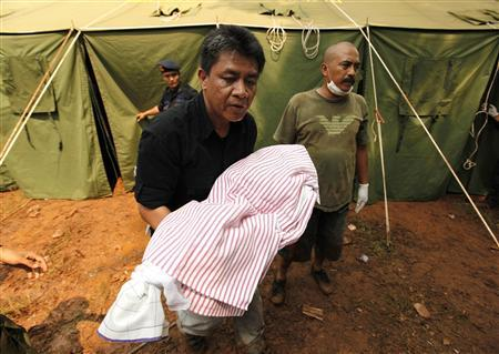 A paramedic carries the body of a child a day after a dam burst on the outskirts of Jakarta March 28, 2009. The death toll from the burst dam which unleashed a wall of water on the outskirts of the Indonesian capital rose to 77 and authorities were searching for than 100 people still missing, officials said on Saturday. REUTERS/Beawiharta