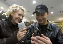 <p>Люди держат в руках телефоны iPhone в магазине в Москве 3 октября 2008 года. Skype, самая популярная служба интернет- телефонии, планирует начать работать на телефонах iPhone во вторник и на телефонах BlackBerry в мае, выйдя за пределы ниши настольных персональных компьютеров. REUTERS/Thomas Peter</p>