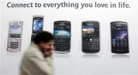 <p>Homem usa celular diante de anúncio da RIM na Alemanha. A Skype, divisão de telefonia via Internet do eBay, está planejando lançar seu serviço para usuários do iPhone na terça-feira e para o BlackBerry em maio, como parte de esforço para se expandir além dos computadores.</p>