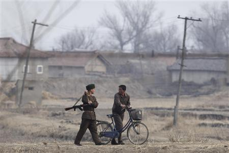 A North Korean soldier walks next to a farmer as he patrols the North Korean-Chinese border near the Chinese border city of Dandong April 4, 2009. REUTERS/ Nir Elias