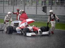 <p>Equipe da manutenção da Toyota ajudam o piloto Jarno Trulli, forçado a parar no Grande Prêmio da Malásia. 05/04/2009. REUTERS/Bazuki Muhammad</p>