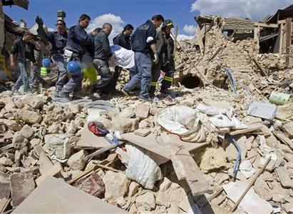 Italian rescue workers carry a body found in the rubble of a collapsed house after an earthquake in the Italian village of Onna April 6, 2009. REUTERS/Chris Helgren