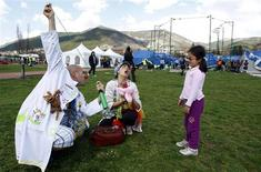 <p>A couple of clowns play with a child in a tent camp where earthquake victims reside in Aquila April 7, 2009. REUTERS/Alessandro Garofalo</p>