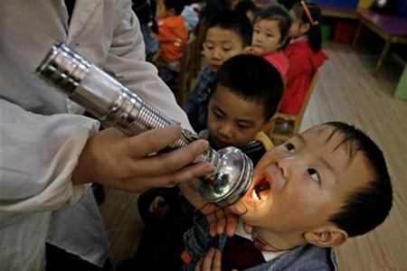 A boy has his mouth checked as part of measures to prevent the hand, foot and mouth disease (HFMD) at a kindergarten in Wuhan, Hubei province April 8, 2009. REUTERS/Stringer