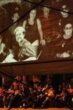 """<p>Imagen de archivo en que personas observan una película durante el Festival Internacional de Cine Pobre, en un parque en Gibara, Cuba, 19 ago 2008. El Festival de Cine Pobre de Gibara, un vibrante espacio para el cine independiente apodado el """"Sundance cubano"""", intentará este mes sobreponerse a la muerte de su fundador Humberto Solás y a la devastación de su pintoresca sede por un huracán. REUTERS/Claudia Dau/Archivo</p>"""