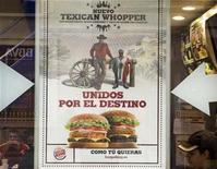 <p>Un afiche de publicidad de Burger King en la ventana de un sucursal de la cadena en Madrid, 14 abr 2009. El gigante de comida rápida Burger King dijo el martes que retirará una publicidad en la que un hombre diminuto con máscara de luchador aparece envuelto en la bandera mexicana, junto a un alto vaquero estadounidense, y que provocó una protesta de México. REUTERS/Paul Hanna</p>