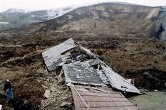 <p>Люди проходят мимо дома, разрушенного оползнем в селе Кара-Тарык в Киргизии 21 апреля 2003 года. Мощный оползень накрыл три дома в селе на юге Киргизии в ночь на четверг, похоронив под собой 16 жителей, сообщил предварительные данные дежурный МЧС Киргизии. REUTERS/Stringer</p>