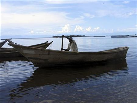 A fisherman paddles his boat on the shores of Lake Albert, October 24, 2007. REUTERS/Tim Cocks