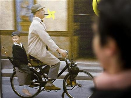 A commuter walks past a poster showing character Mr. Hulot played by French actor/director Jacques Tati, smoking a windmill toy which replaces his emblematic pipe, in the metro in Paris April 17, 2009. REUTERS/Philippe Wojazer