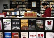 <p>A Chinese man reads a book as another walks between shelves at the 'Utopia' bookshop in central Beijing in this March 25, 2009 file picture. REUTERS/David Gray /Files</p>