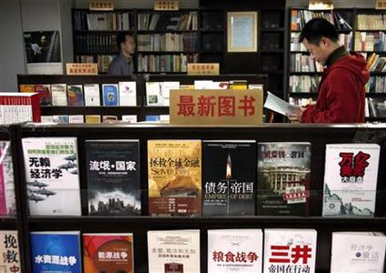 A Chinese man reads a book as another walks between shelves at the 'Utopia' bookshop in central Beijing in this March 25, 2009 file picture. REUTERS/David Gray /Files