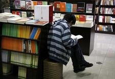 <p>A Chinese man sits between shelves of books as he reads at the 'Utopia' bookshop in central Beijing in this March 25, 2009 file picture. REUTERS/David Gray/Files</p>