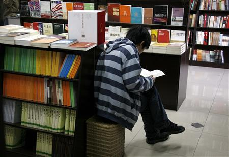 A Chinese man sits between shelves of books as he reads at the 'Utopia' bookshop in central Beijing in this March 25, 2009 file picture. REUTERS/David Gray/Files