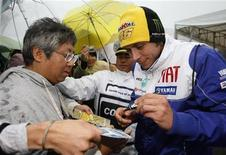 <p>Il campione del mondo di MotoGP Valentino Rossi firma autografi a Motegi, a nord di Tokyo. REUTERS/Issei Kato</p>