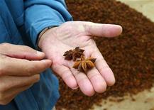 """<p>Человек держит в руках семена звездчатого аниса в Гулуне, провинция Гуанси 18 марта 2005 года. Боитесь, что ваше любимое блюдо из свинины может стать источником свиного гриппа? Министр здравоохранения Китая советует добавлять в пищу немного звездчатого аниса, в России известного под названием """"бадьян"""". REUTERS/John Ruwitch</p>"""