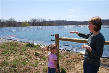 Stephanie Hallowich (R) and her daughter Alison look out over a three-acre reservoir supplying water to natural gas-drilling operations around her house in Hickory, Pennsylvania, April 23, 2009. REUTERS/Jon Hurdle