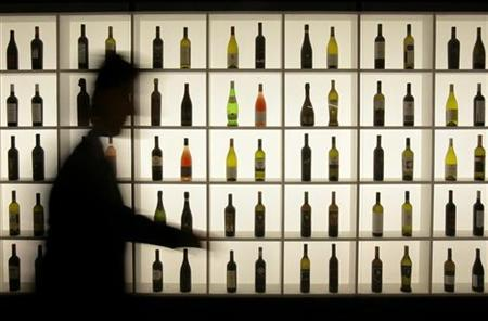 A man passes bottles on display at the Vinitaly wine expo in Verona April 4, 2008. REUTERS/Alessandro Garofalo