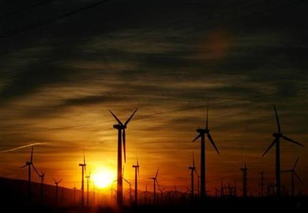The sun rises over a windmill farm in Palm Springs, California, November 27, 2005. REUTERS/Lucy Nicholson