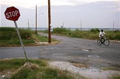 <p>A man cycles past vacant lots near the site where the levee was breached during Hurricane Katrina in the Lower Ninth Ward of New Orleans, in a 2007 photo. REUTERS/Lee Celano</p>