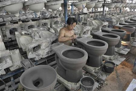 A labourer works on a toilet bowl for export, at a ceramic factory in Tangshan, Hebei province, October 15, 2008. REUTERS/Stringer