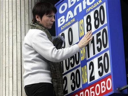 A woman changes the rates of a currency exchange rate board in Kiev, February 26, 2009. REUTERS/Konstantin Chernichkin