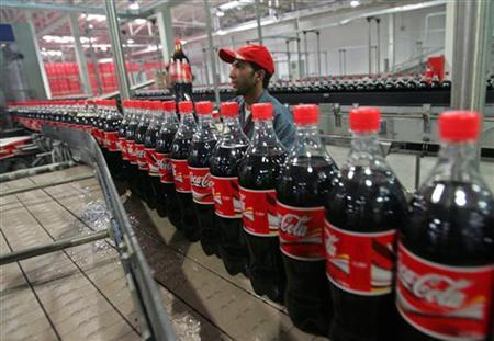A worker checks bottles of Coca-Cola at the newly inaugurated bottling plant in Kabul September 10, 2006. REUTERS/Ahmad Masood