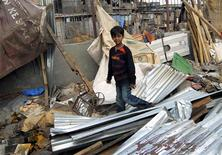 "<p>Azharuddin Ismail, who acted as the young 'Salim' in the Oscar-winning movie ""Slumdog Millionaire"", walks through the debris after his home was demolished by local authorities, at a slum area in Mumbai May 14, 2009. REUTERS/Stringer</p>"