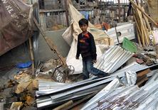 <p>Azharuddin Ismail, star di Slumdog Millionaire, cammina sui resti della sua casa demolita dalle autorità di Mumbai. REUTERS/Stringer</p>