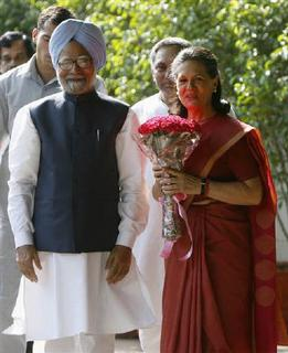Congress Party chief Sonia Gandhi holds a bouquet presented by Prime Minister of India Manmohan Singh (L) prior to their meeting at her residence in New Delhi May 16, 2009. REUTERS/Adnan Abidi