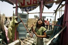 """<p>Rubina Ali (C), who acted as young Latika in the Oscar-winning movie """"Slumdog Millionaire"""", looks around as her house gets demolished by local authorities, at a slum area in Mumbai May 20, 2009. REUTERS/Punit Paranjpe</p>"""
