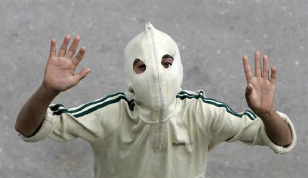 A Masked Supporter of the moderate faction of Kashmir's Hurriyat (freedom) Conference gestures during a rally to mark the anniversary of Mirwaiz Mohammad Farooq's death in Srinagar May 21, 2009. REUTERS/Danish Ismail