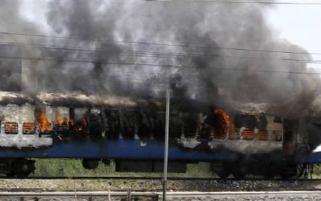 A passenger train burns in Jalandhar, in Punjab May 25, 2009. Troops patrolled towns and highways in Punjab to enforce a curfew on Tuesday after three people were killed in riots sparked by the killing of a Sikh preacher in Austria. REUTERS/Stringer