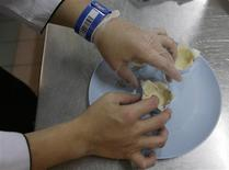 <p>An inmate, wearing a barcoded identification bracelet, prepares a dish during a cooking competition at a kitchen inside Changi Prison in Singapore May 26, 2009. REUTERS/Vivek Prakash</p>