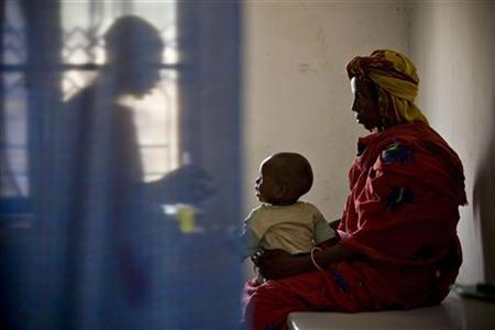 A doctor (L) administers medicine to a sick child with his mother at a health clinic run by the medical charity Medecins Sans Frontieres (MSF) Holland in Kerfi, a site for displaced Chadians some 50 kilometers (30 miles) south of the eastern town of Gos Beida, June 10, 2008. REUTERS/Finbarr O'Reilly