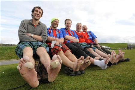 Inverness Caledonian Football Club supporters pose for the camera during an annual charity walk from the venue of the penultimate game of the season to the venue of the last game, at Ruthven Barracks, near Newtonmore, Scotland in this photo taken May 20, 2009. REUTERS/Russell Cheyne