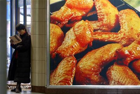 A Chinese woman reads newspaper beside an advertisement for a U.S. fried chicken fast-food chain in Shanghai, January 16, 2004. REUTERS/Claro Cortes