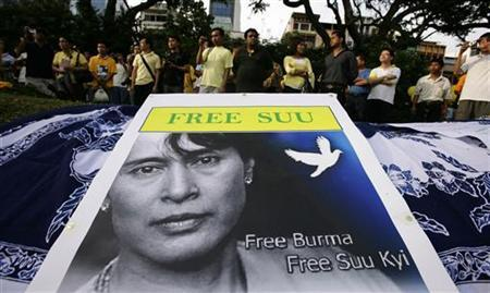 People stand behind a poster as they gather to call for the release of Aung San Suu Kyi at the Speaker's Corner in Singapore May 31, 2009. REUTERS/Vivek Prakash