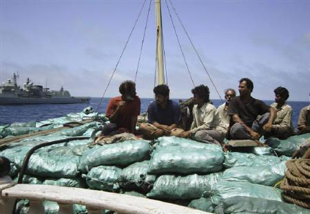 The rescued crew of Indian dhow Vishvakalyan sits on top of their cargo of charcoal as they receive assistance from NATO's Portuguese flagship NRP Corte-Real (background) June 13, 2009. REUTERS/Alison Bevege
