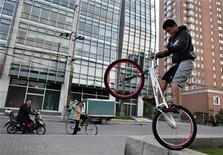 <p>Человек исполняет трюки на велосипеде в Шанхае 26 апреля 2009 года. Китаец изобрел велосипед, колеса которого выполнены в форме треугольника и пятиугольника. REUTERS/ Nir Elias</p>