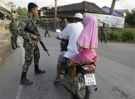 Soldiers guard a village after a police raid in which suspected Muslim militants were killed in southern Thailand's Yala province, about 1,084 km (674 miles) south of Bangkok June 18, 2009. In the rustic villages of Thailand's Muslim south, Prime Minister Abhisit Vejjajiva's promise of large-scale development aid to tackle a brutal insurgency sounds all too familiar. Four suspected Muslim militants were killed on Thursday during the raid, police said after a 30-minute gunbattle. He said they had received a tip that militants were using a house in the area as a hideout. REUTERS/Surapan Boonthanom
