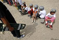 """<p>Дети из первой в Афганистане школе по скейтборлингу """"Skateistan"""" ждут начала спортивного праздника в Кабуле 21 июня 2009 года. Трудно было узнать столицу Афганистана в воскресенье: десятки мальчиков и девочек на скейтбордах двигались по улицам города, сопровождаемые полицейским эскортом. REUTERS/Ahmad Masood</p>"""
