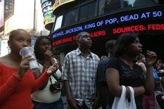 <p>Personas observan el reporte de la muerte del cantante Michael Jackson en Times Square en Nueva York, 25 jun 2009. REUTERS/Eric Thayer</p>