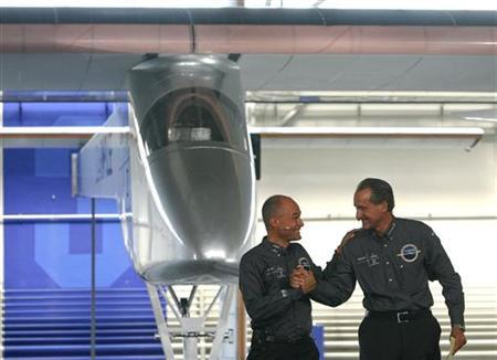 Bertrand Piccard (L), pilot and president of Solar Impulse and Andre Borschberg, CEO and pilot of the company, congratulate each others during the unveiling ceremony of the the solar-powered 61 metres (200 feet) wingspan HB-SIA prototype airplane at the airport in Duebendorf near Zurich June 26, 2009. REUTERS/Arnd Wiegmann